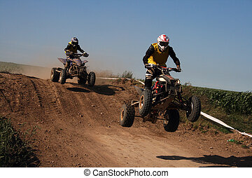 Quad race series - Professional quad biker jumping during...