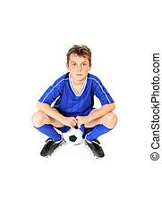 Soccer player resting on soccer ball.