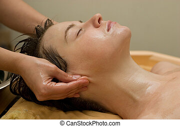ayurvedic oil massage procedure - young woman on the...