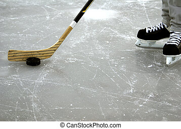 Hockey - a hockey stick and puck and ice skates on the ice