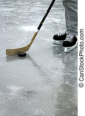 Ice Hockey - a hockey stick and puck and ice skates on the...