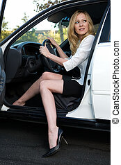 Woman in car - Pretty blond woman in white blouse and black...
