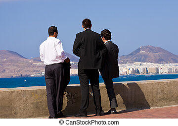 Business men - Team of three young business men looking at...