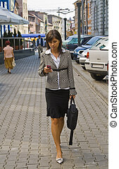 Businesswoman checking her mobile while she is walking.