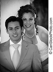 us - young bride and groom pose close together