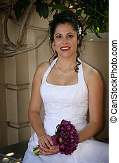 sitting bride - bride sits while holding her bouquet