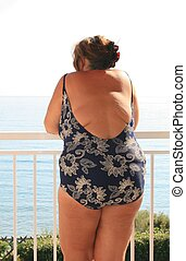 Obese woman in bathing suite looking at the ocean