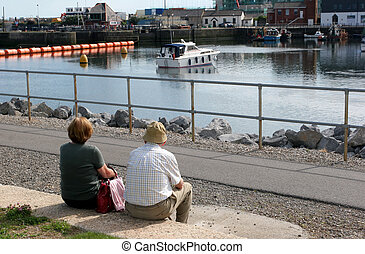 Peaceful Together - Elderly man and woman sitting together...