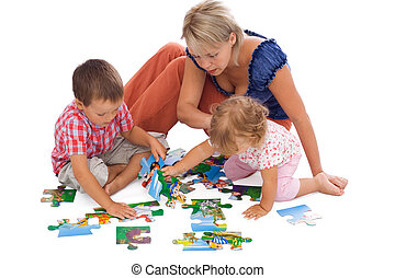 Family playing with puzzle - Family, woman and kids, playing...