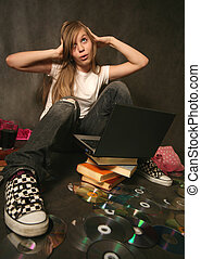 Girl with a computer - The young girl among books with a...