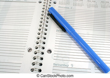 Blue highlighter and day planner - a Blue highlighter and...