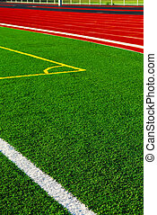 Track and field - Red racetrack and green sports field with...