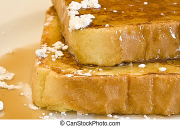 french toast on a white plate with powdered sugar and maple...
