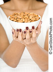Bowl of Nuts - A woman holding a ceramic bowl of almond nuts...