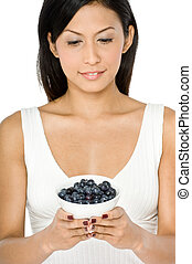 Woman With Blueberries - A pretty young Asian woman holding...