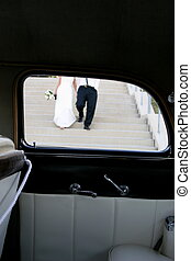Wedding Walk - A couple walks to their car after their...