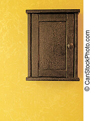 antique key box with crackled paint hanging on a golden wall...