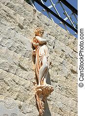 Statuette - Pretty greek girl statuette on the garden wall.
