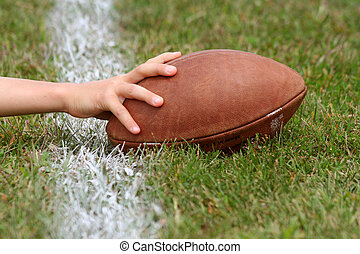 Touchdown - hand with football reaching over white line