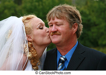 bride kissing daddy - bride kissing her father on the cheek.