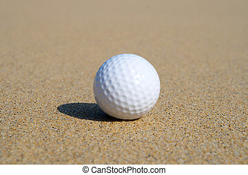 A golf ball in the sand with shallow focus