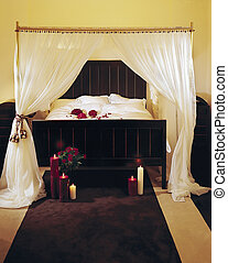 a fancy bed with a canopy, candles and dried flowers