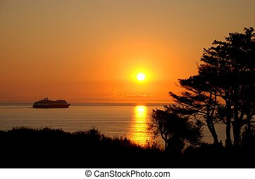 Sunset and Cruise Ship - A cruise ship sails on a calm ocean...