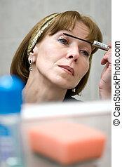 mature woman put mascara on