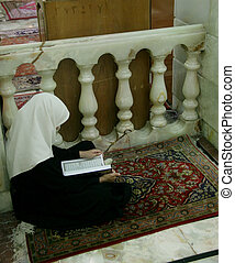 Veiled girl with Quran - A veiled girl studying the Quran on...