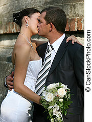 Newly married pair - The groom and the bride kiss in park