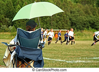 Soccar Mom - A mom sits and watches the kids play soccer in...
