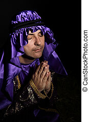 Worshipping man - Man arrayed in purple and gold with hands...