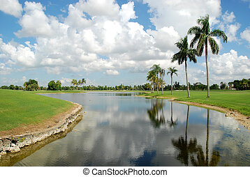 Canal - Palm trees reflected in a canal at a golf course,...