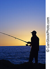 Silhouette of Fisherman at sunset at Cottesloe beach , Perth