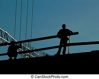 Men at work - Silhouette of construction workers on a roof...