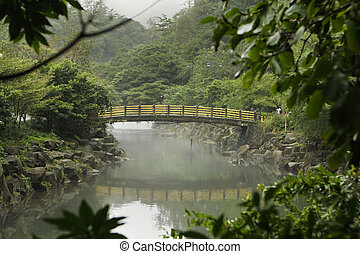 Bridge In Korea - A bridge with yellow railings crosses over...