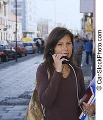 Urban communication - Beautiful young woman using a public...