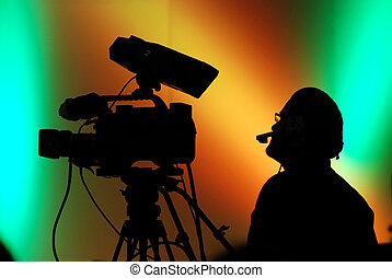 Camera man working on a show,his silhouette is in front of a...