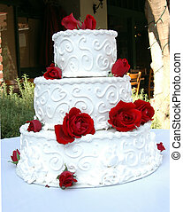 Full view of wedding cake - A white wedding cake with scroll...
