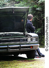 Delay - A man waits for a tow truck by his broken down car.