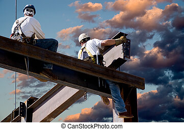 Dawn Workers - Two ironworkers atop the skeleton of a modern...
