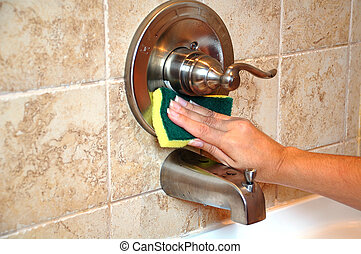 Cleaning time - View of hand cleaning a bathtub faucet