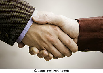 business handshake - close up, focus point on center of the...