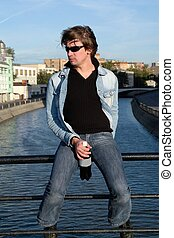 Cool dude with a bottle against the river