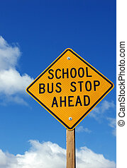 Bus Stop Sign - School bus stop ahead sign with a cloudy sky...