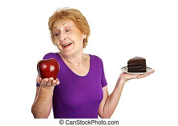 Healthy Choice - Fit senior lady choosing a healthy apple...