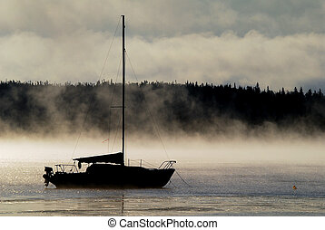 Sailing into the Mist - Silhouette of a sailboat in the...