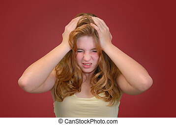 Pain - Teenager holding her head with anguished expression...