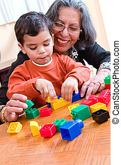 Playing with Grandma - A child plays with his blocks while...