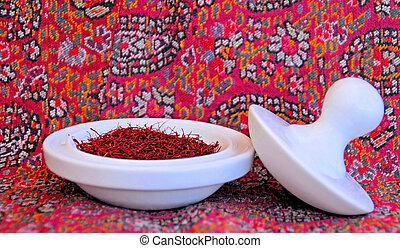 saffron spice in pestal and mortor with red paisely...